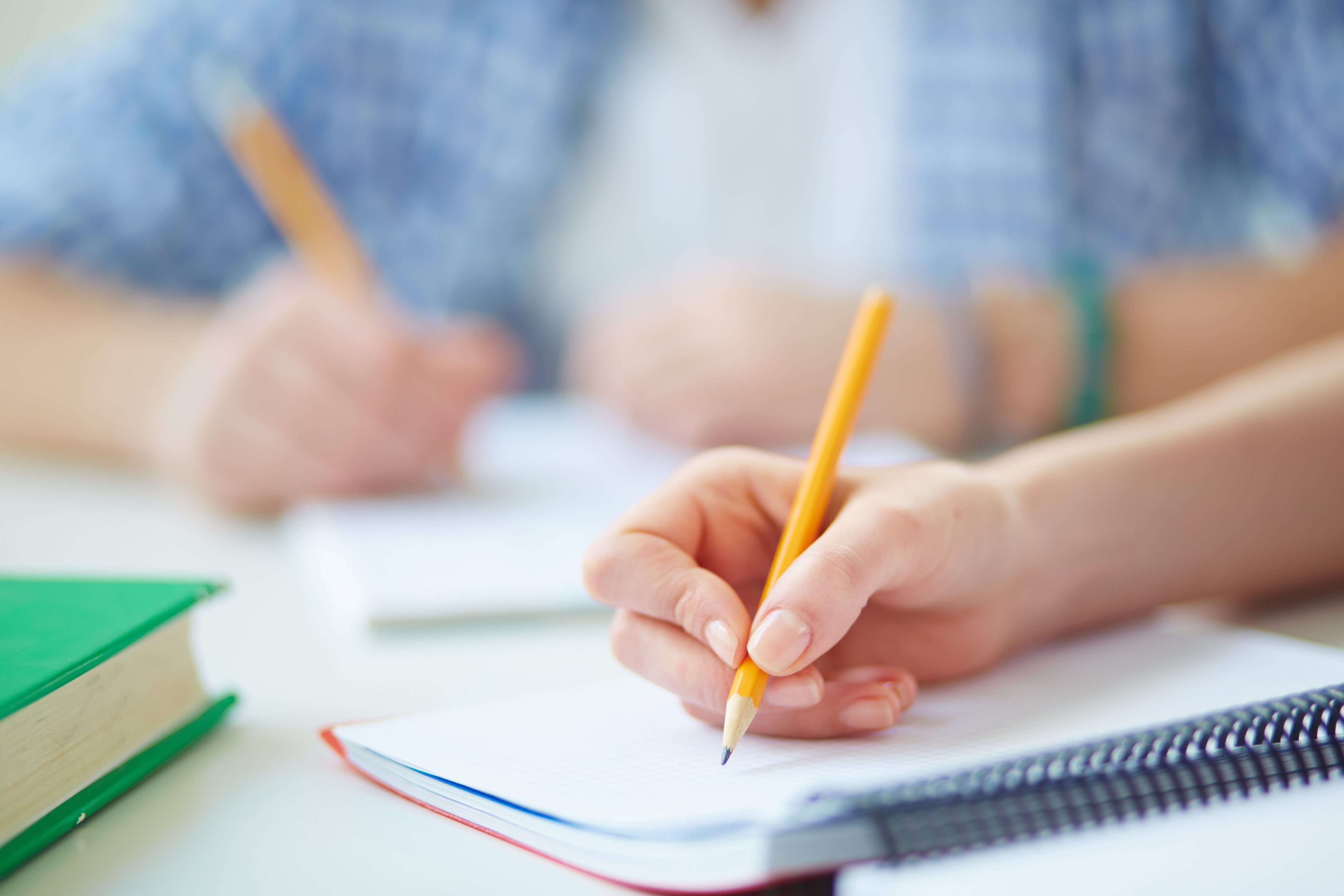 student writing with pencil in a notebook